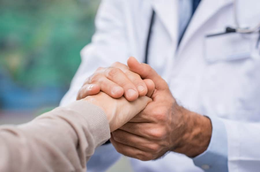 Close up of doctor hand reassuring her female patient at hospital. Closeup hands of medical doctor carefully holding patient's hands. Kind doctor giving real support for patient symbolizing care for those with chronic health conditions