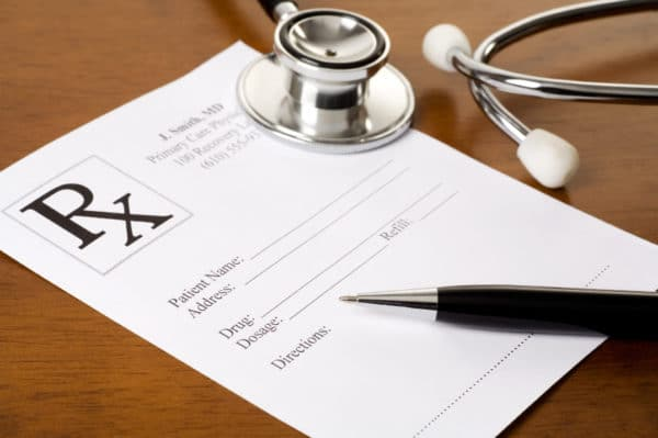 A prescription form, pen, and stethoscope on a doctor's desk.