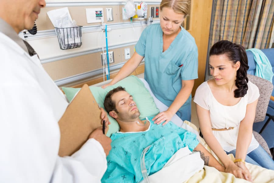 Woman Holding Patient's Hand While Doctor And Nurse Examining Hi